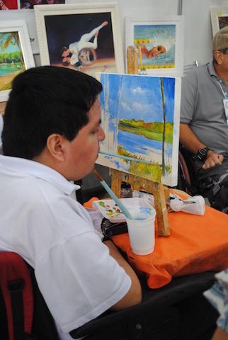Artista que usa a boca para pintar faz demonstração